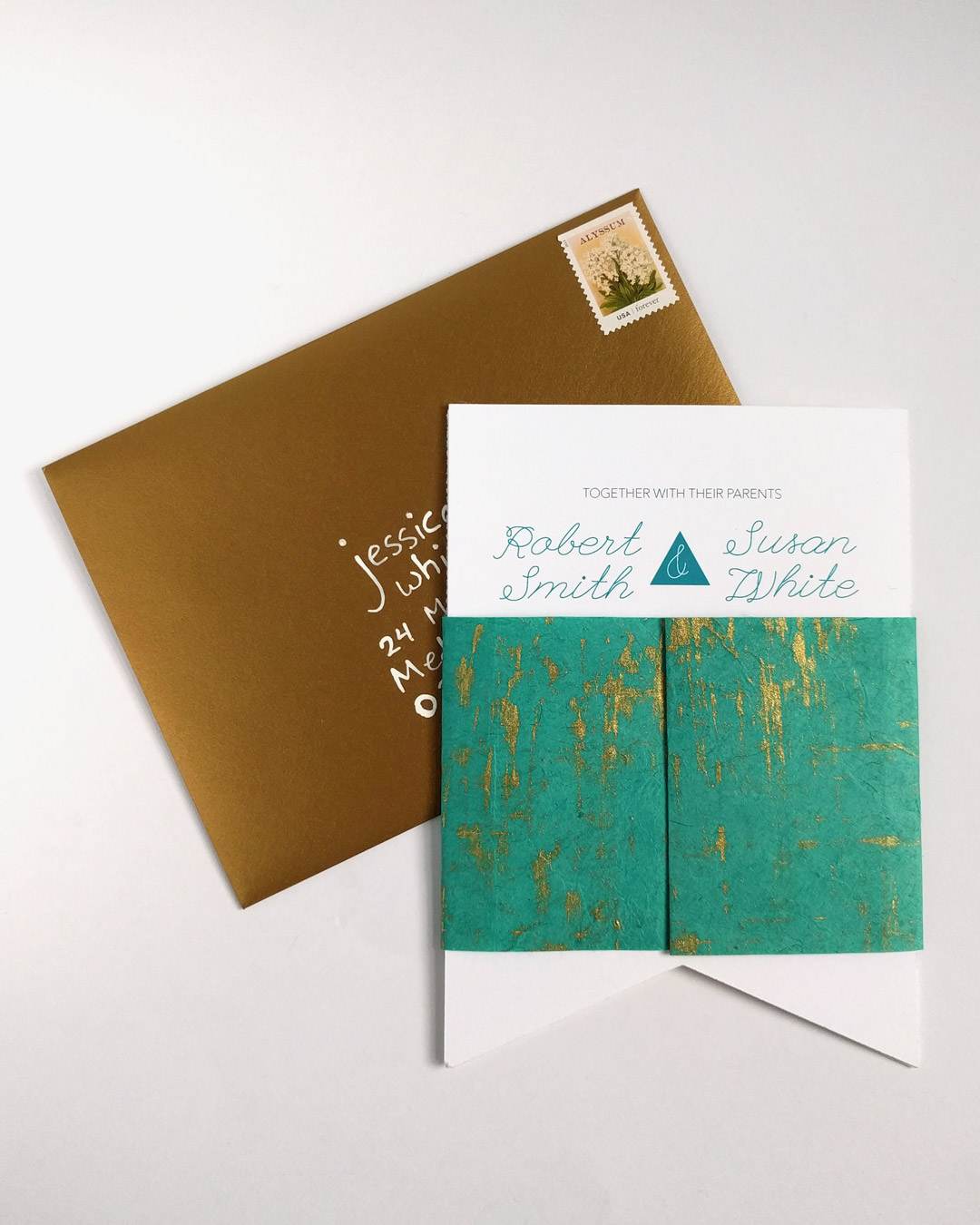 Custom wedding invitation with handmade paper belly band and gold envelope