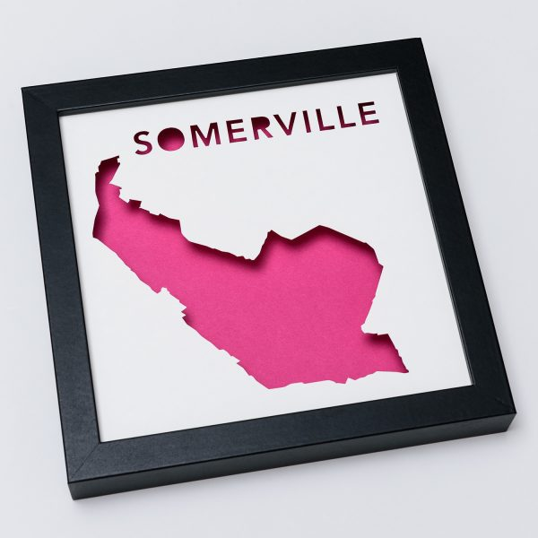 Framed map of Somerville, MA cut out to reveal a bright pink background.