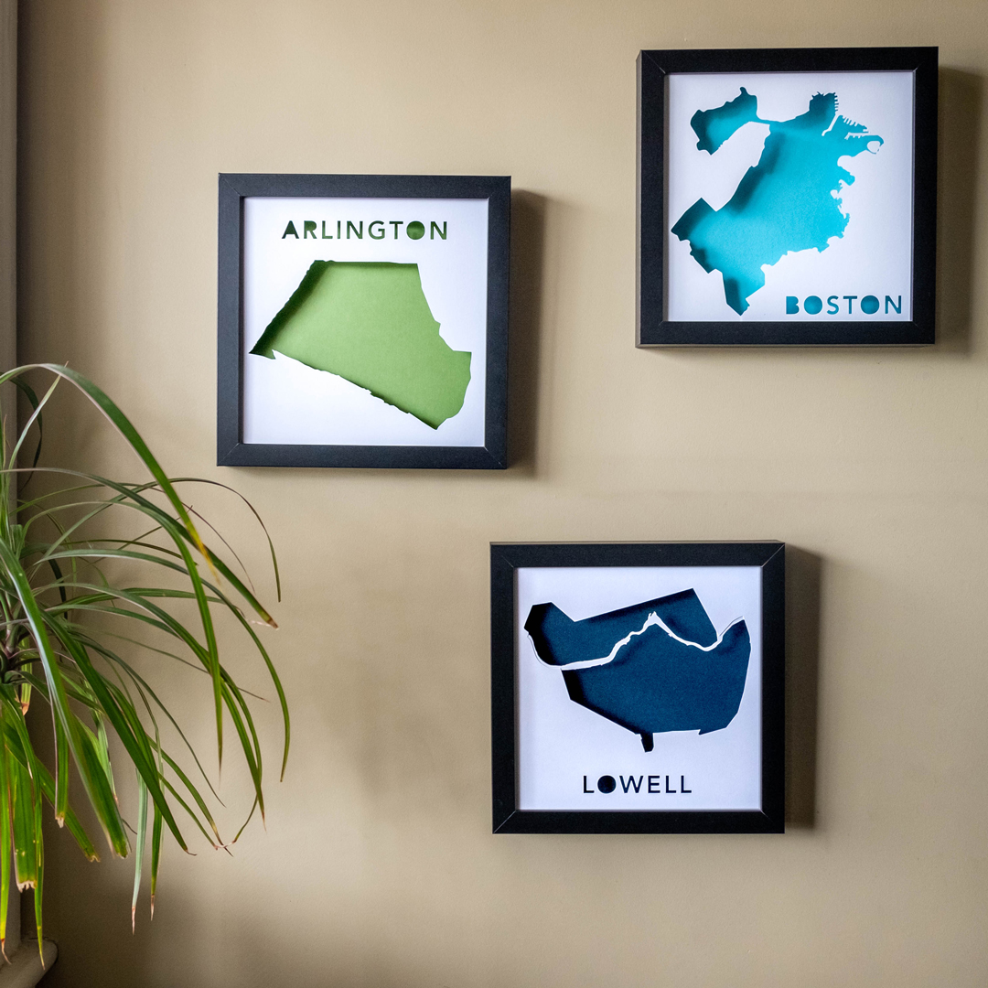 Three framed paper places on a wall near a potted plant