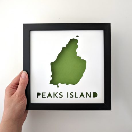 Framed map of Peaks Island with a green background, held in hand