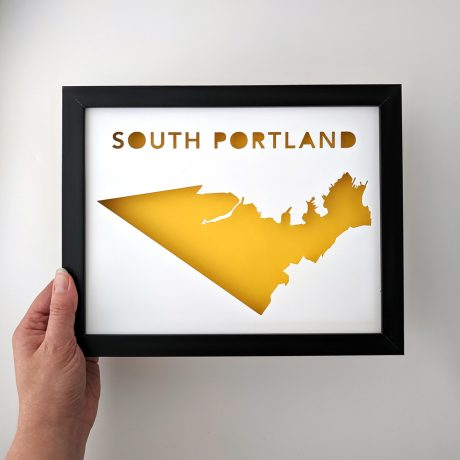 South Portland map with yellow background in black frame held in hand