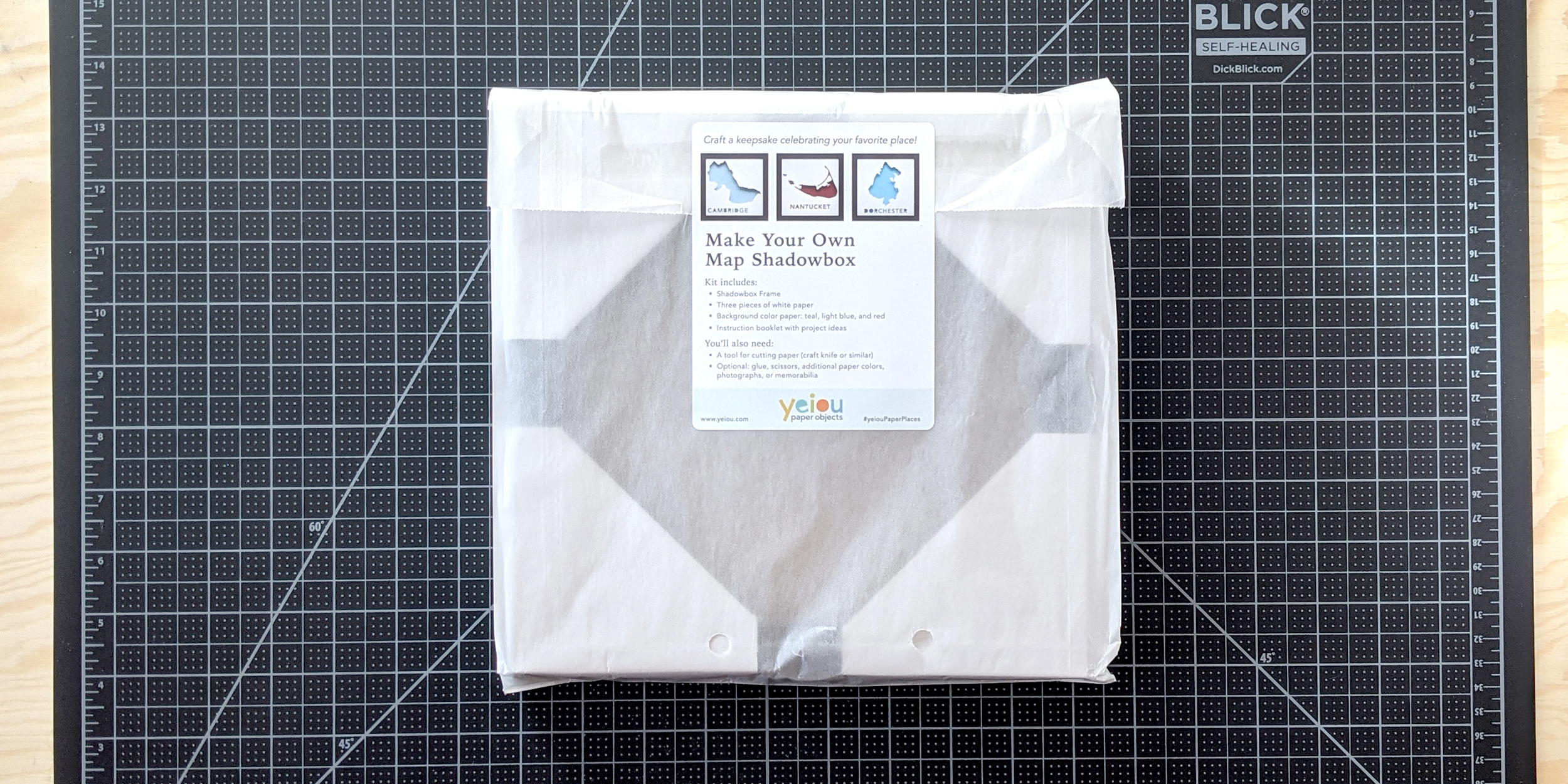 Packaged Make Your Own Paper Place kit on a desk