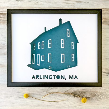 Framed house portrait silhouette depicting a three-story duplex labeled Arlington, MA. Silhouette has a teal background, and frame is sitting on a woodgrain background.