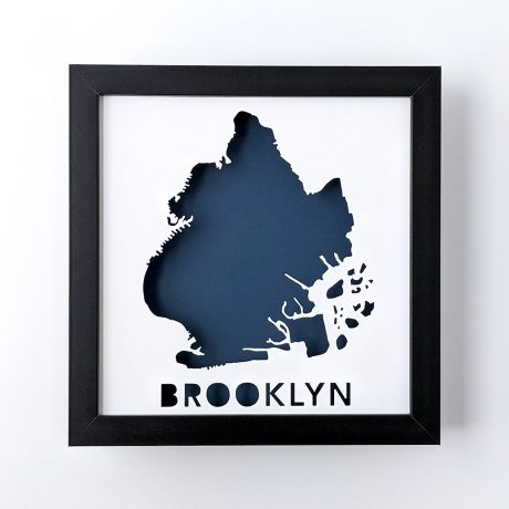 Framed map of Brooklyn, NYC cut out of white paper revealing a dark blue background
