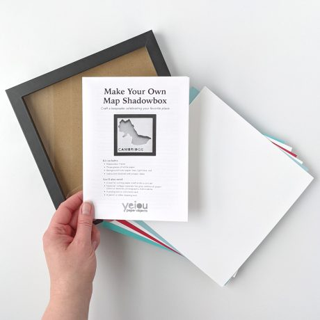 """Paper Place Kit Contents: black 8x8"""" frame, white paper, colored background paper, and instruction booklet"""