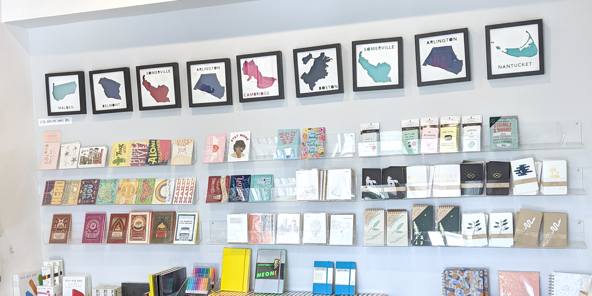 A variety of framed paper places on the wall of Tiny Turns Paperie in Somerville, MA above a display of postcards and notebooks